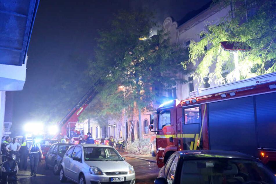 Feuerwehrleute löschen von einem Löschkorb aus den Dachstuhl des brennenden Hauses in Krefeld.