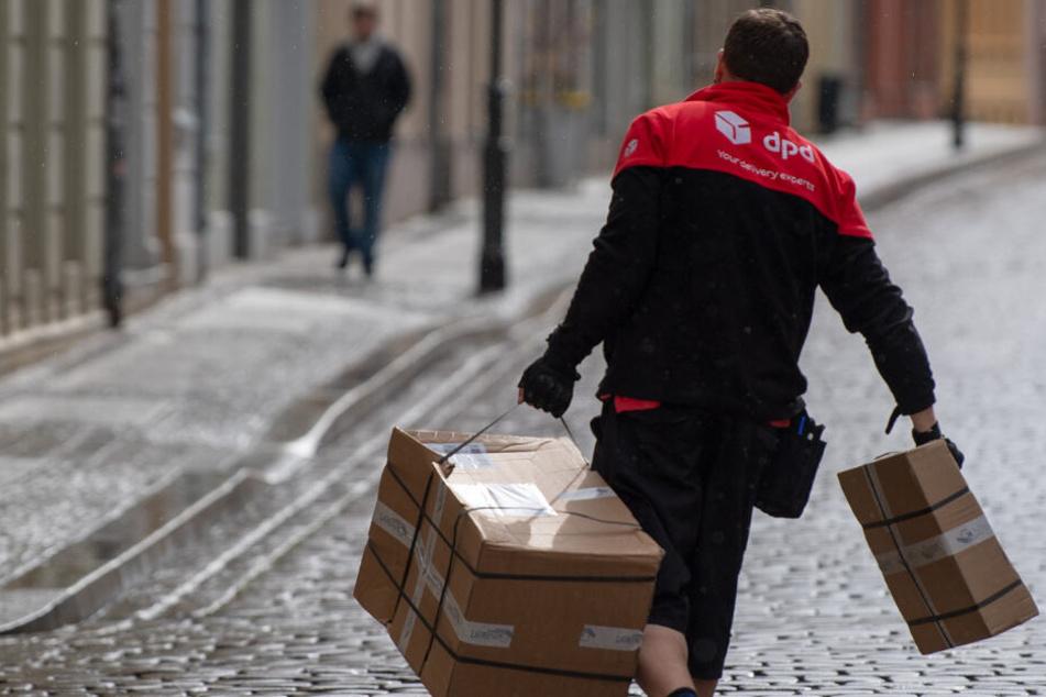 Ein DPD-Mitarbeiter hat zwei Pakete in seinen Händen.