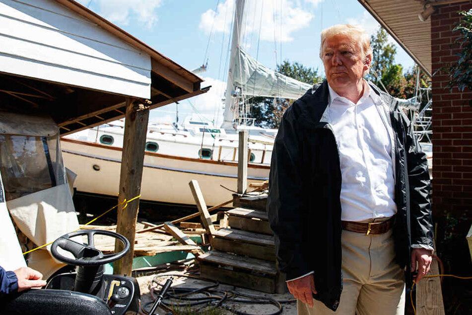 Präsident Donald Trump besucht ein Haus, in dem ein Boot im Hinterhof an Land gespült wurde.