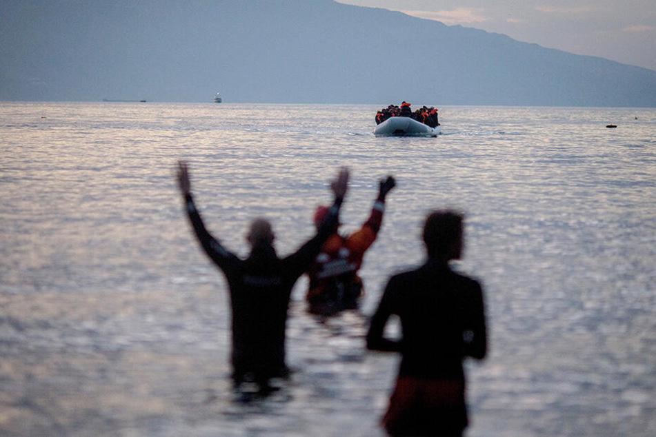 Flüchtlinge kommen in einem Schlauchboot aus der Türkei auf der griechischen Insel Lesbos in der Nähe der Hafenstadt Mitilini (Griechenland) an und werden von Helfern erwartet.