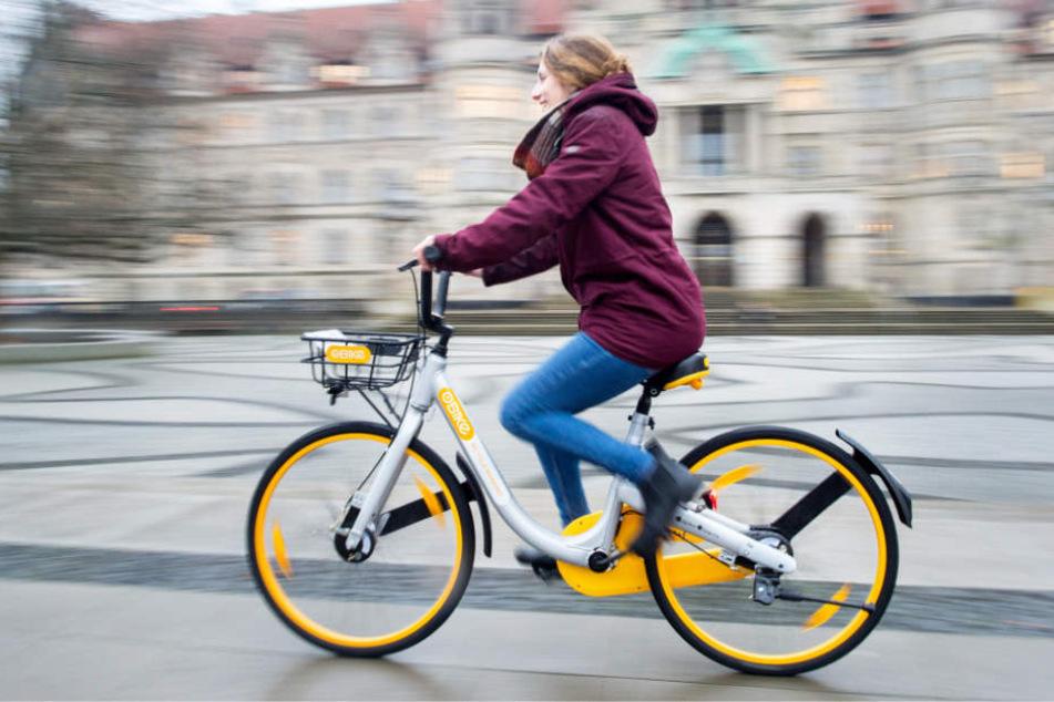 Eine Frau vor dem Neuen Rathaus in Hannover mit einem Leihfahrrad der Firma Obike