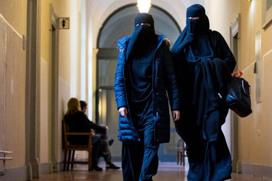 Zwei Frauen mit Nikab-Vollschleier gehen zum Beginn der Hauptverhandlung im Strafverfahren gegen sechs mutmaßliche Salafisten in den Gerichtssaal im Strafjustizgebäude in Hamburg.