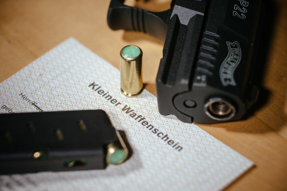 """Ein Kleiner Waffenschein liegt am zwischen einer Schreckschuss-Pistole """"Walther P22"""", einem Magazin und einer Knallpatrone (Symbolbild)."""