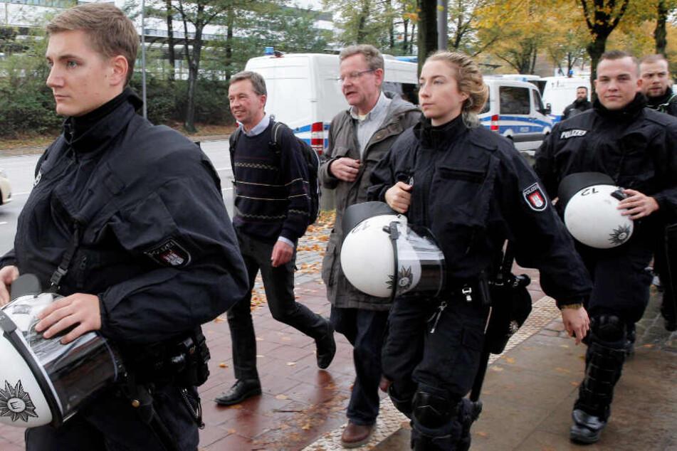 Unter Polizeischutz verlässt Bernd Lucke die Uni Hamburg.