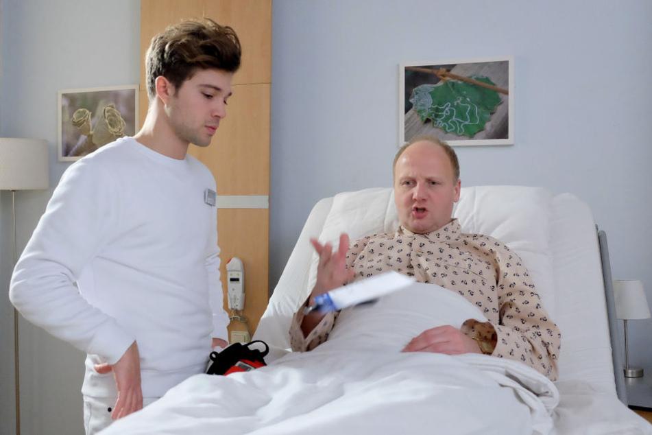 IaF-Folge 812: Kris Haas (Jascha Rust, l.) soll Patient Ole Beck (Christian Hockenbrink, r.) ein Langzeit-EKG anlegen. Doch der zeigt sich nicht gerade kooperativ.