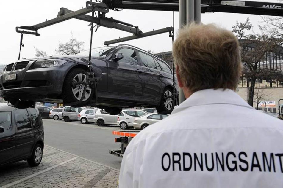 Ein Mitarbeiter des Ordnungsamtes lasst einen BMW abschleppen (Archivfoto).