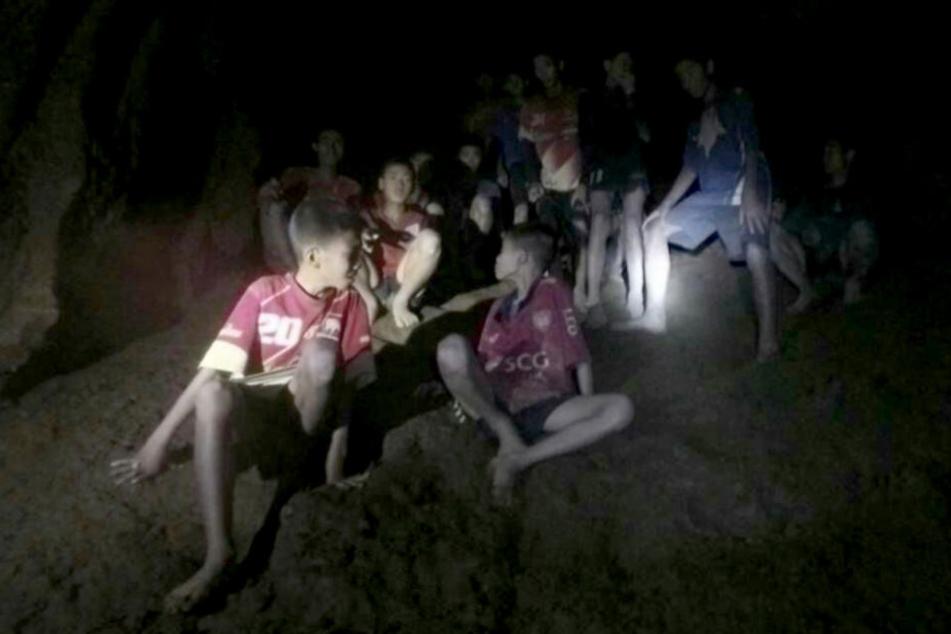 Eine der Thai Navy Seals zur Verfügung gestellte Aufnahme zeigt die vermissten Jugendfußballer und ihren Trainer, nachdem sie in einer Höhle entdeckt wurden.