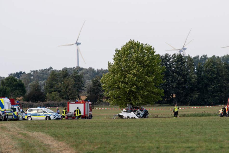 Einsatzkräfte der Feuerwehr und der Polizei stehen nach dem Absturz von einem Kleinflugzeug auf einem Feld zwischen dem Ortsteil Badingen und Gransee.