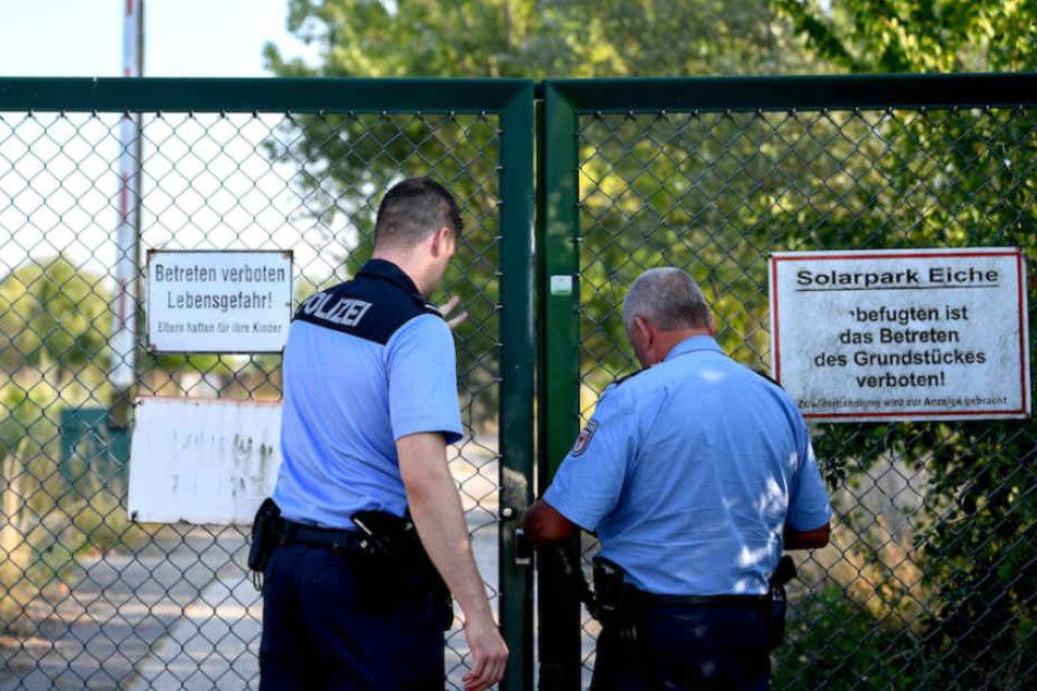 Polizisten schließen das Tor zum Gelände, auf dem die Leiche gefunden wurde.