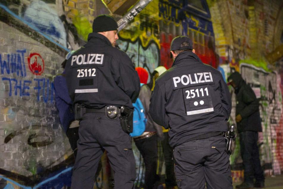 Polizisten stehen im Jahr 2014 bei einer Polizeiaktion im Görlitzer Park vor Personen, die kontrolliert werden sollen.