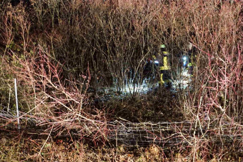 Einsatzkräfte im Gebüsch. Der Benz hatte auch den Zaun im Vordergrund noch deutlich sichtbar demoliert.