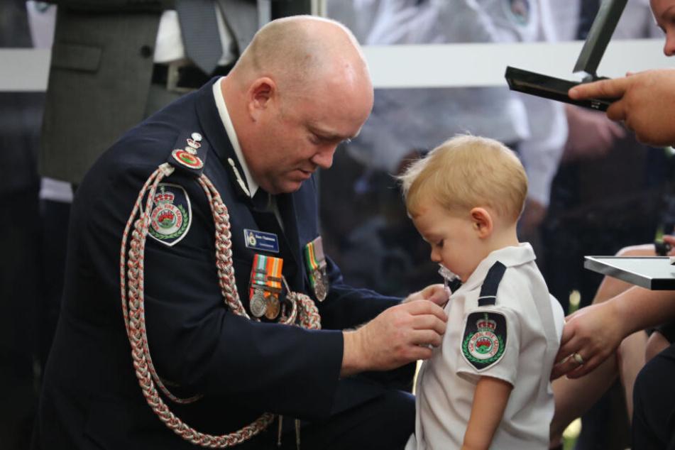 Kommissar Shane Fitzsimmons (l.) überreicht dem Sohn des freiwilligen Feuerwehrmannes Geoffrey Keaton bei dessen Beerdigung stellvertretend eine posthume Auszeichnung für seinen mutigen Einsatz.