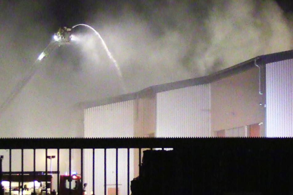 Feuerwehrleute löschen die brennende Halle mit Abfall.