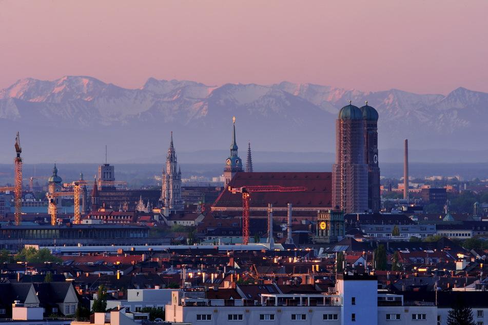 Zum Greifen nah. Die Münchner Frauenkirche vor dem verschneiten Alpenpanorama.