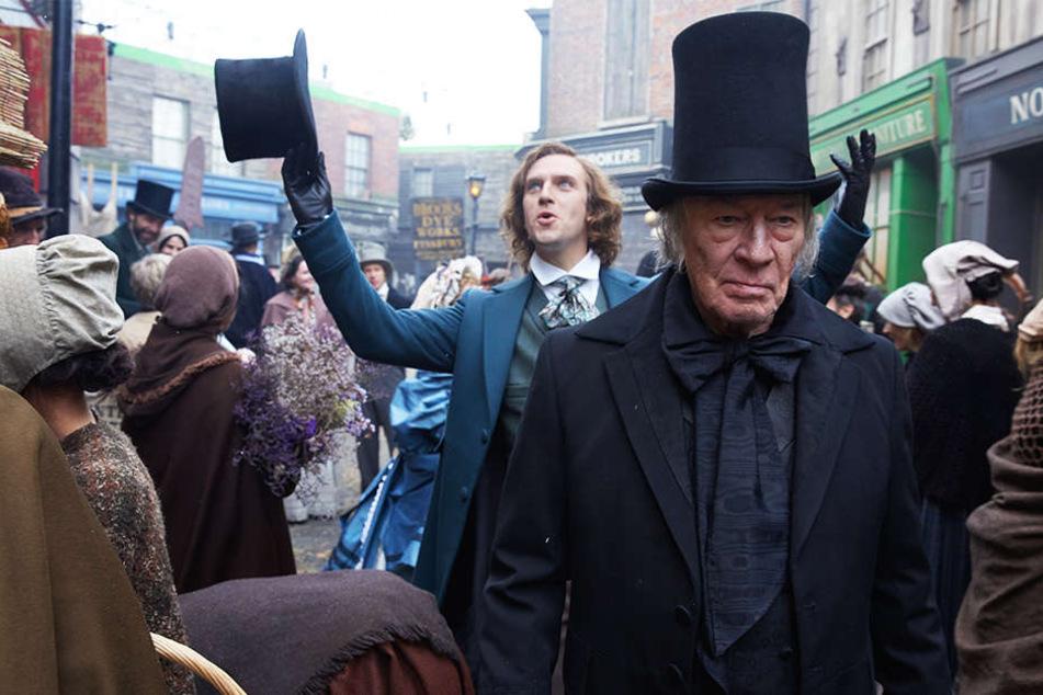Scrooge (r., Christopher Plummer) ist stets missgelaunt, während Charles Dickens (Dan Stevens) mit offenen Armen und Augen durch die Welt geht.