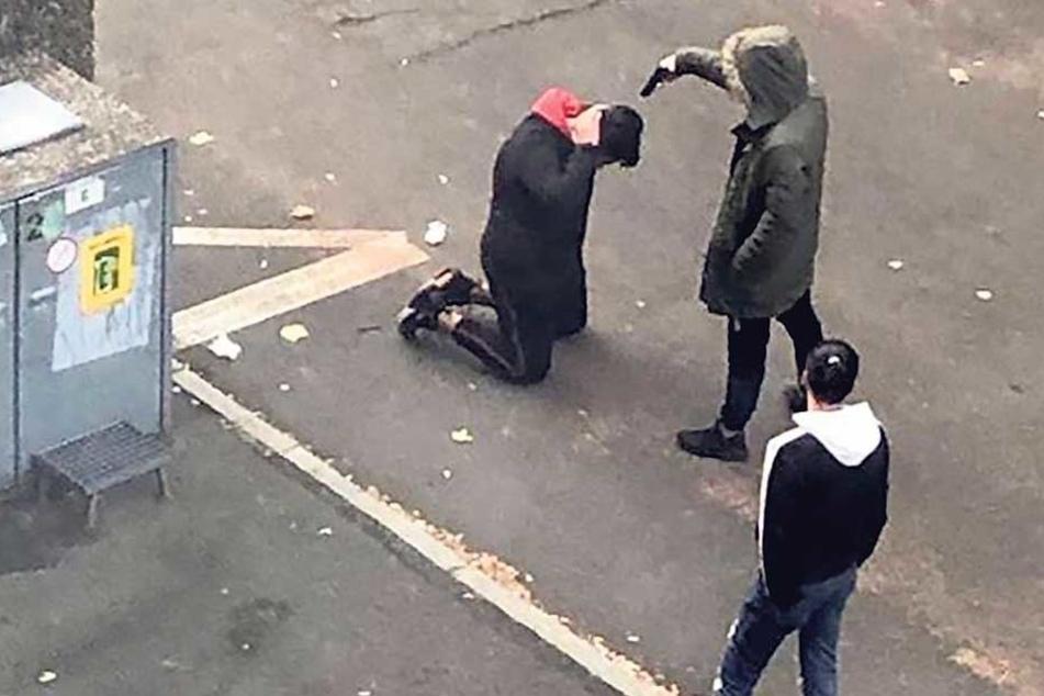 """Schockierende Aufnahme: Auf dem Asphalt kniet das """"Opfer"""" der Schein-Hinrichtung, der Pistolenmann zielt auf den Kopf."""