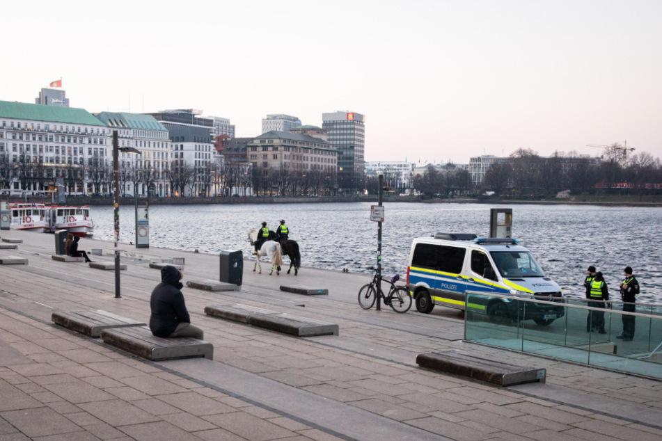 Nur wenige Menschen sind am Abend am Jungfernstieg unterwegs während Polizeibeamte die Maßnahmen gegen die Ausbreitung des Coronavirus kontrolieren.