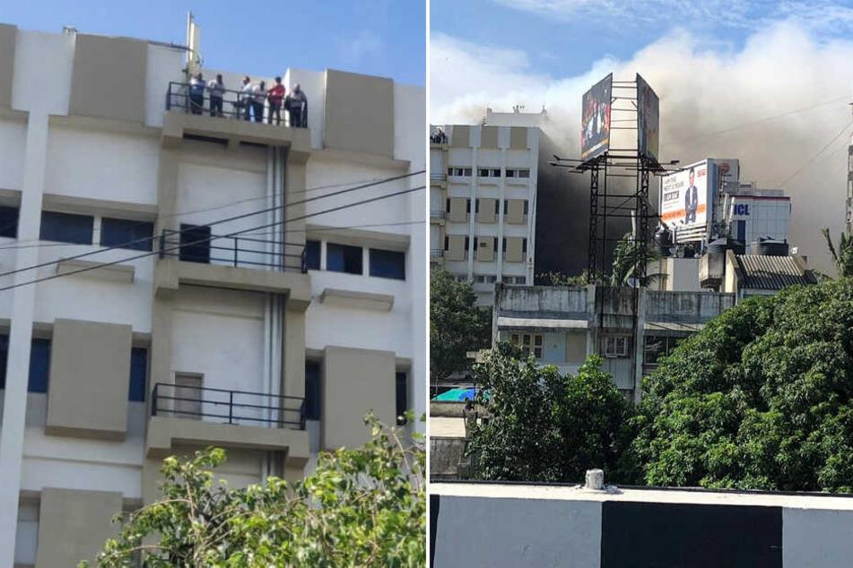 Mehrere Personen warten auf einem Balkon auf ihre Rettung, während es im Gebäude brennt.