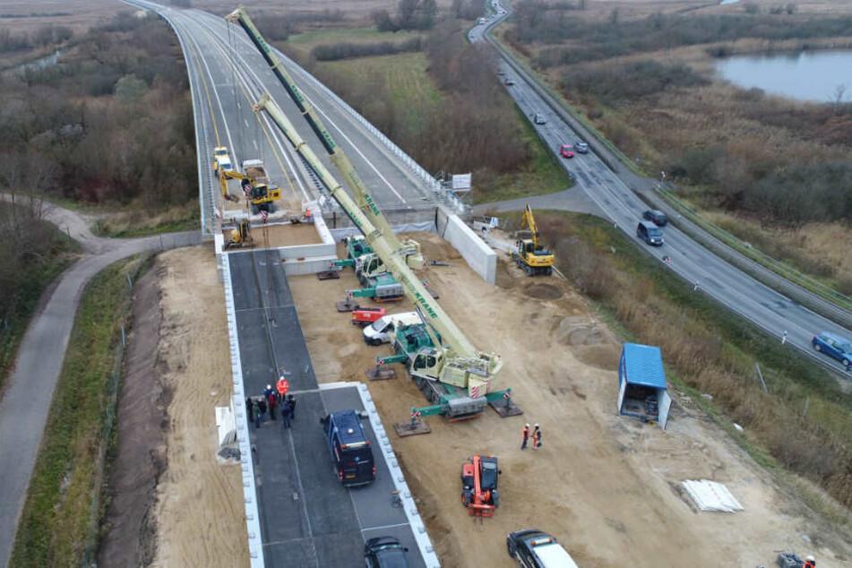 An der Behelfsbrücke für die abgesackte Autobahn A20 wird das letzte Bauteil verlegt.