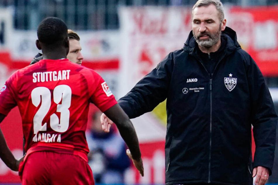 Stuttgarts Trainer Tim Walter (r) geht nach Pleite gegen Sandhausen zu Stuttgarts Orel Mangala.