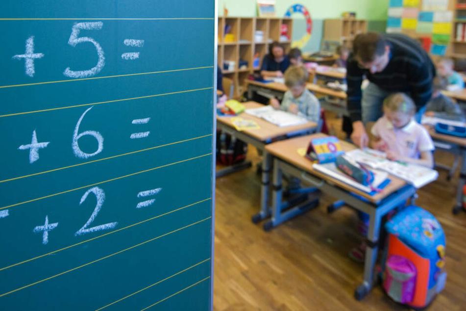 Ein Lehrer hilft einer Grundschülerin bei ihren Aufgaben. (Symbolbild)