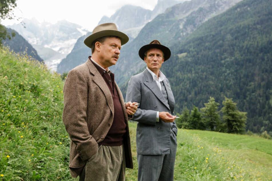 Julius (l., Justus von Dohnányi) und Arthur Kemper (Oliver Masucci) besprechen die schwere Lage vor den malerischen Schweizer Berglandschaften.