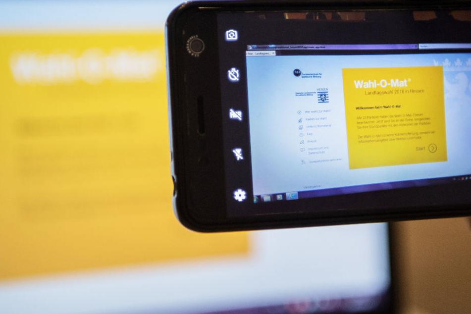 """Ein Nutzer macht mit dem Smartphone ein Foto vom hessischen """"Wahl-O-Mat"""" auf einem Laptop."""