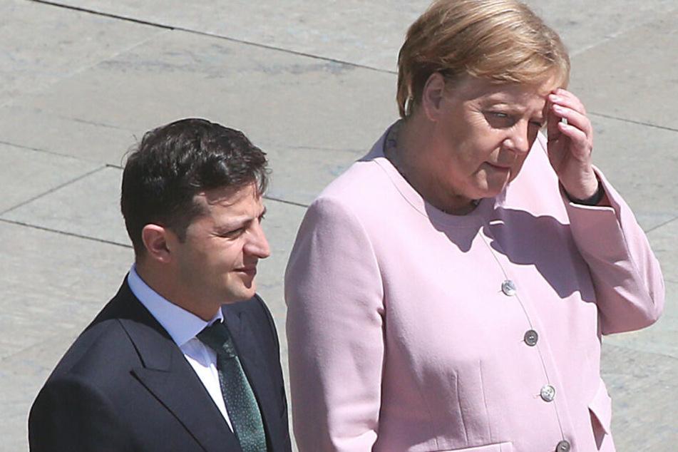 Merkel und Selensky verfolgen die Nationalhymne.
