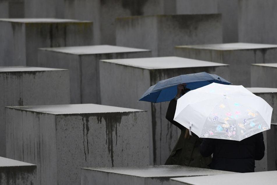 Touristinnen besuchen bei regnerischem Wetter am Holocaust-Mahnmal in Berlin.