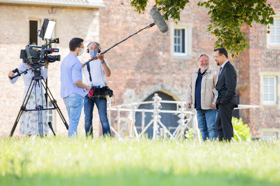 """Jan Josef Liefers (r), Schauspieler (als Karl-Friedrich Boerne), und Axel Prahl, Schauspieler (als Frank Thiel), geben einem Fernsehteam vom WDR bei Dreharbeiten zum """"Tatort"""" aus Münster """"Es lebe der König"""" vor Schloß Hülchrath ein Interview."""