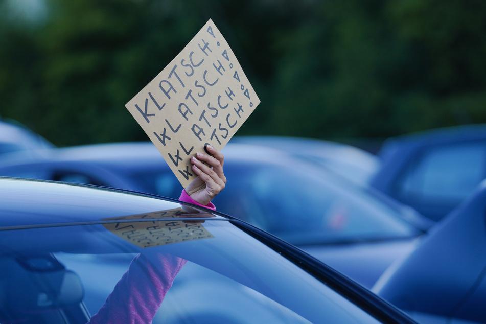 """Eine Zuschauerin hält bei einem Auftritt des Comedian Bülent Ceylan im Autokino beim """"Car-watch-Festival"""" mit seinem Programm """"OPEN hAIR SPEZIAL"""" ein Plakat mit der Aufschrift """"Klatsch! Klatsch! Klatsch! Klatsch!"""" aus dem Autofenster."""
