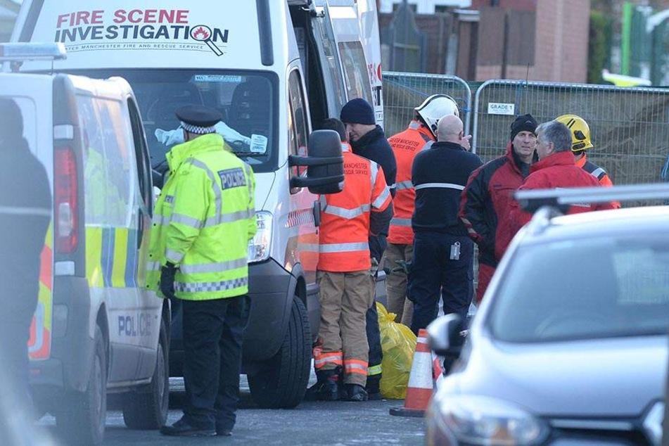 Einsatzkräfte stehen am Ort des Hausbrandes in der Jackson Street in Worsley.