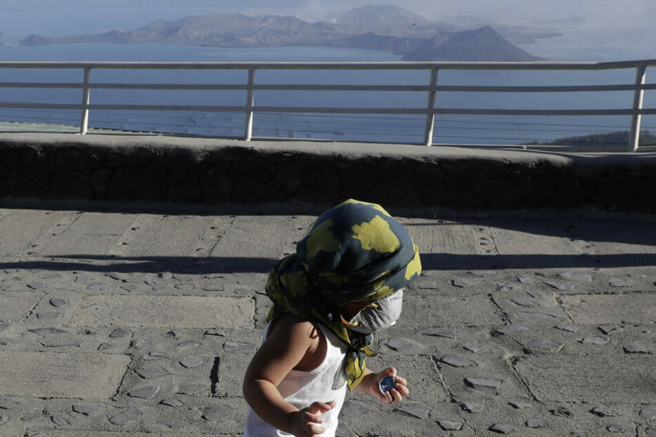"""Ein Kind mit Atemmaske und Kopfbedeckung läuft über einen Gehweg. Im Hintergrund sieht man den Vulkan """"Taal""""."""