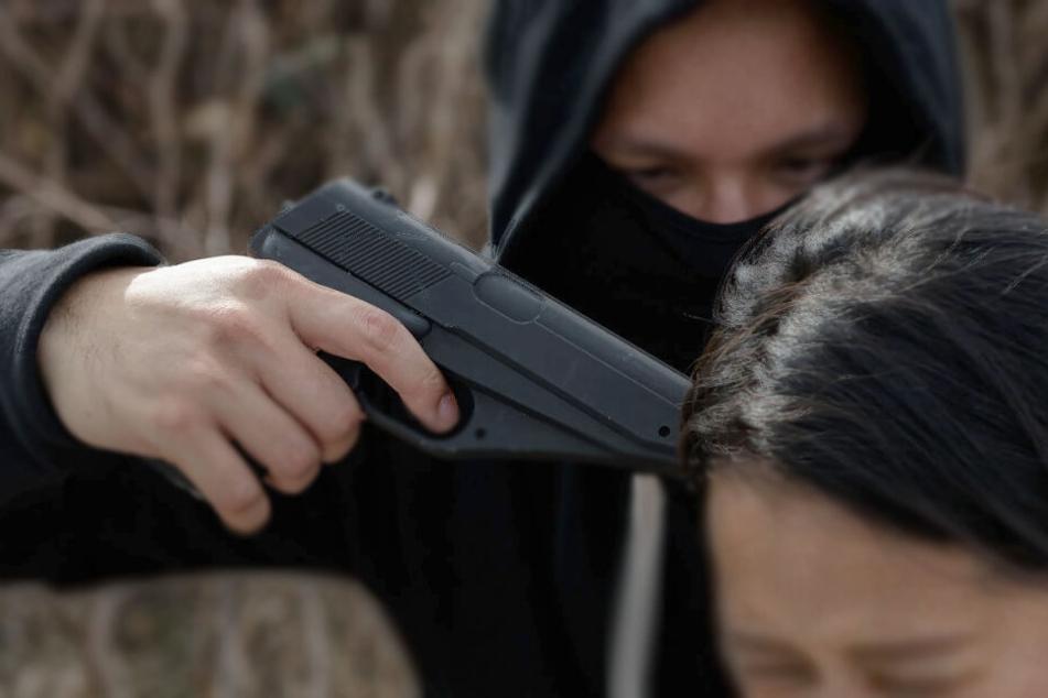 Mann drückt Frau Waffe an den Kopf und bedroht sie. (Symbolbild)
