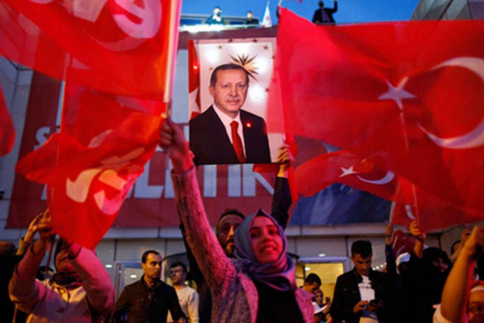 Unterstützer der türkischen Regierungspartei APK wedeln mit Fahnen und halten ein Plakat Erdogans hoch.