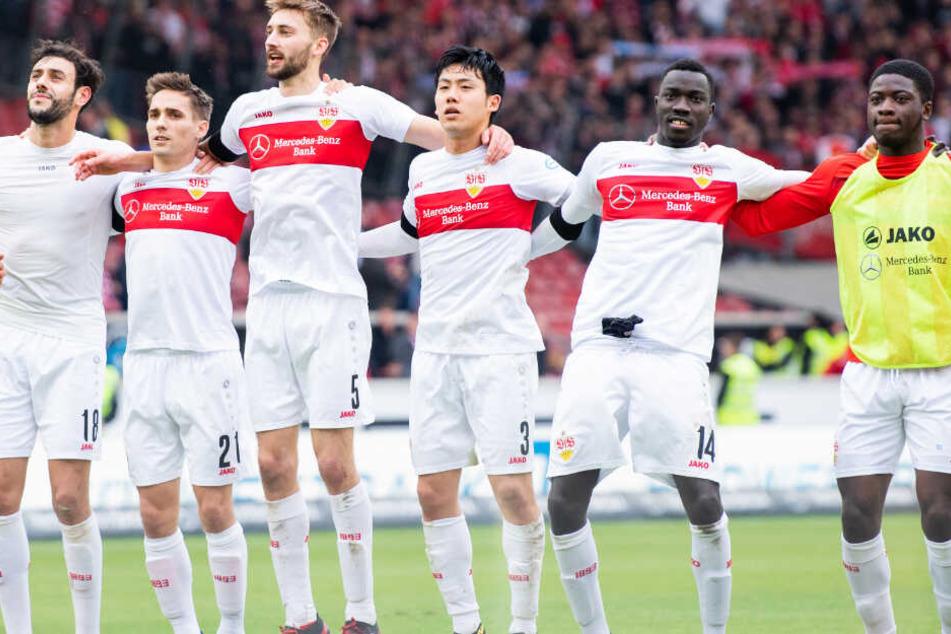 VfB-Sieger feiern vor der Cannstatter Kurve: Hamadi Al Ghaddioui (l-r), Philipp Klement, Nathaniel Phillips, Wataru Endo, Silas Wamangituka und Clinton Mola.