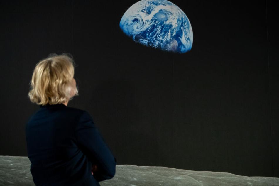 """Eine Frau betrachet während der Ausstellung das aus der Apollo 8 aufgenomme Bild """"Earthrise""""."""