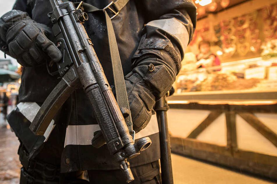 Mit einer Maschinenpistole bewaffneter Polizist auf einem Weihnachtsmarkt.