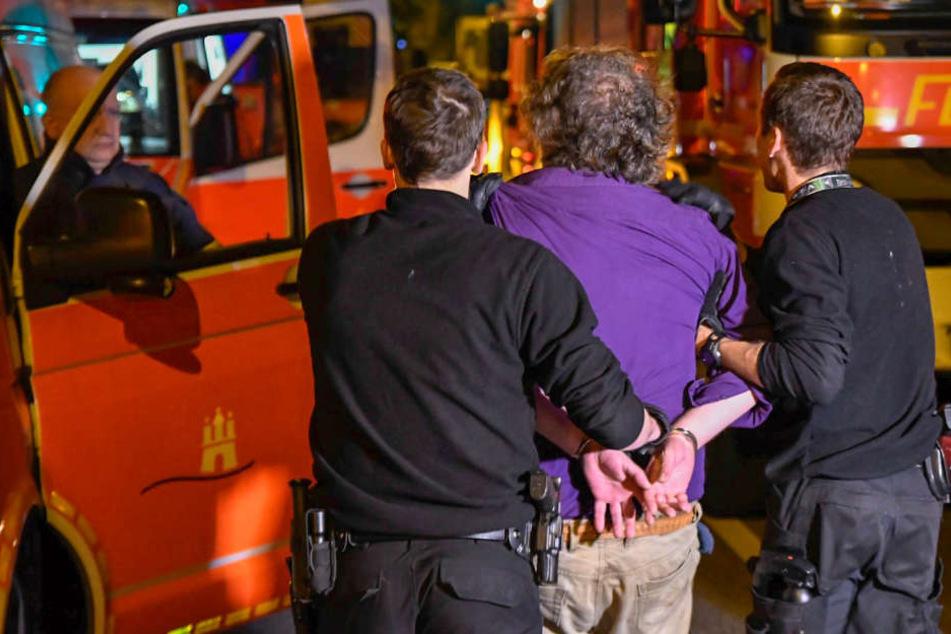 Beamte der Polizei führen den Mann ab. Zuvor hatte er sich in seiner Wohnung verschanzt.