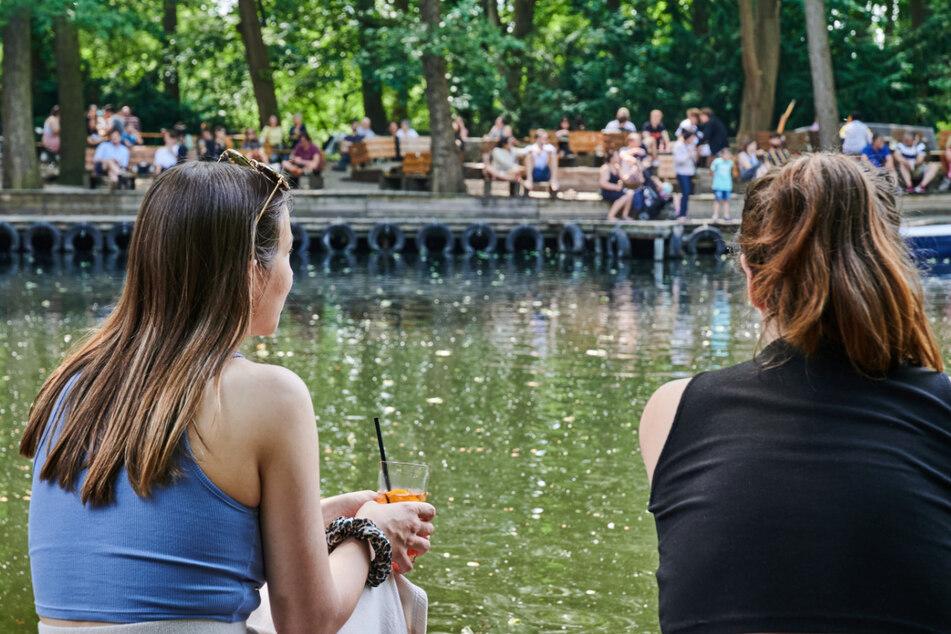 Zwei Frauen sitzen am Wasser im Cafe am Neuen See und genießen das gute Wetter.