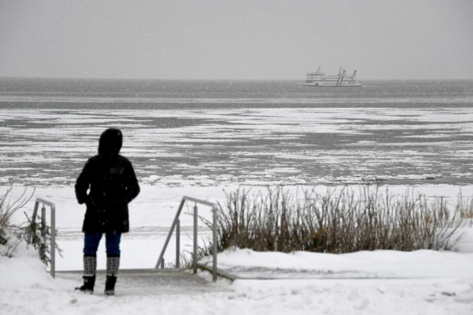 Eine Fußgängerin steht am Strand im Schnee. (Symbolbild)