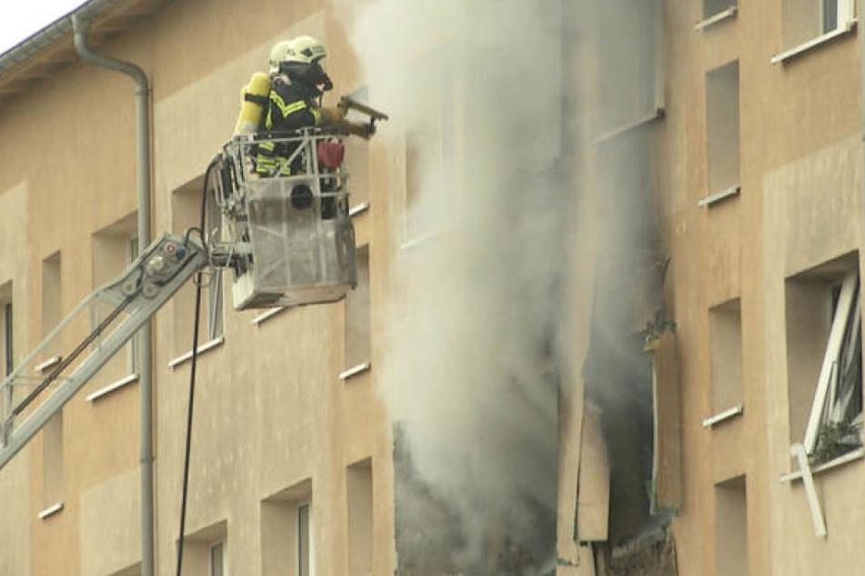 Zwei Feuerwehrkameraden stehen im Oktober auf einer Drehleiter und löschen die brennende Wohnung. Der Mieter Denis S. (29) soll sie selbst angezündet haben.