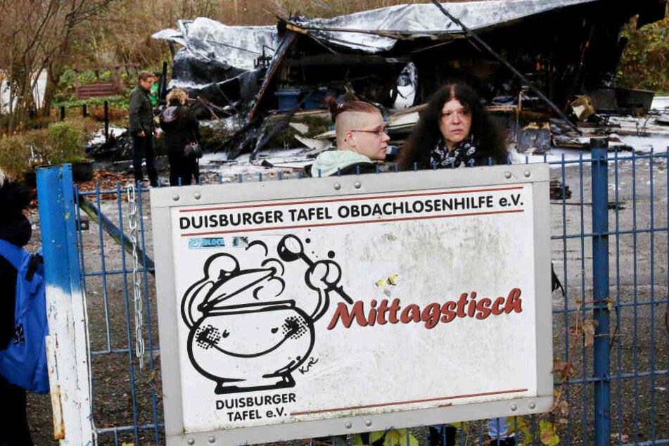 Tafel-Leiterin Petra Klein (r) und ihre Tochter Svenja Klein stehen vor der von einem Feuer zerstörten Essensausgabe der Duisburger Tafel.