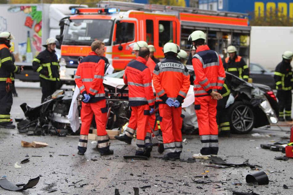Einsatzkräfte stehen vor dem Unfallfahrzeug am Kaltenkircher Platz.