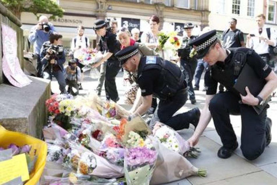 Polizisten legen auf der St Ann's Square in Manchester Blumen ab.