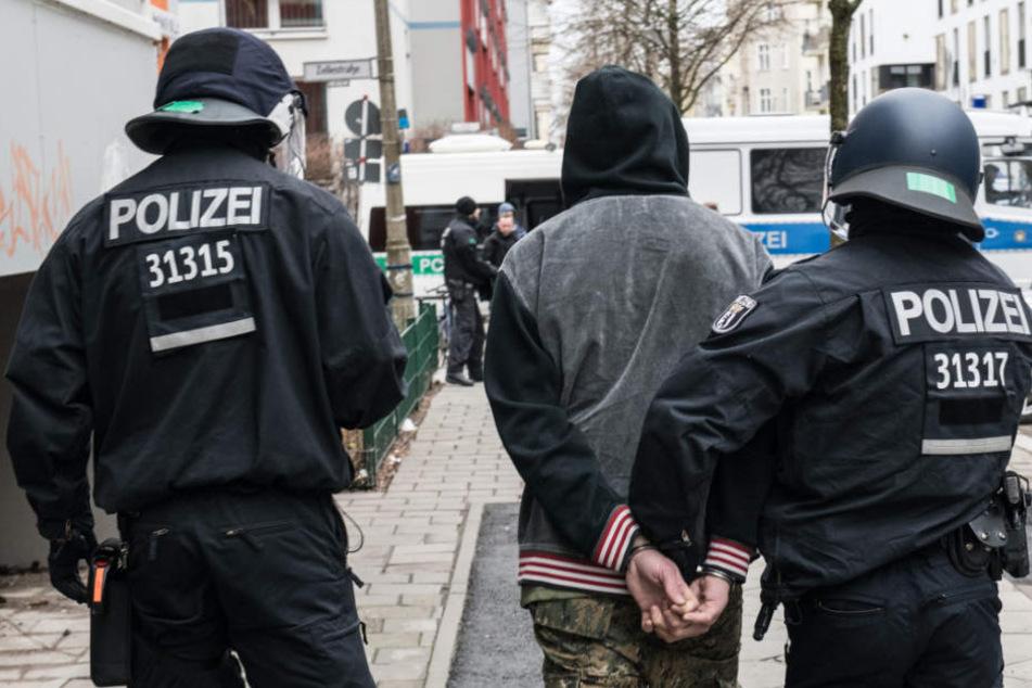 Polizeibeamte führen einen Gewalttäter, gegen den ein Haftbefehl vorlag, ab.