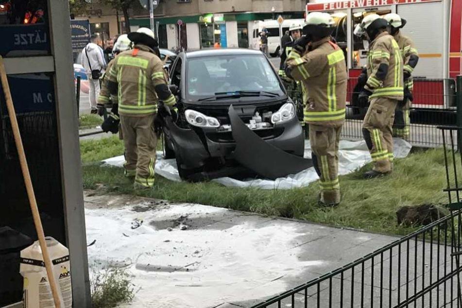 Rettungskräfte an der Unfallstelle, an der der Smart den Zaun durchbrach.