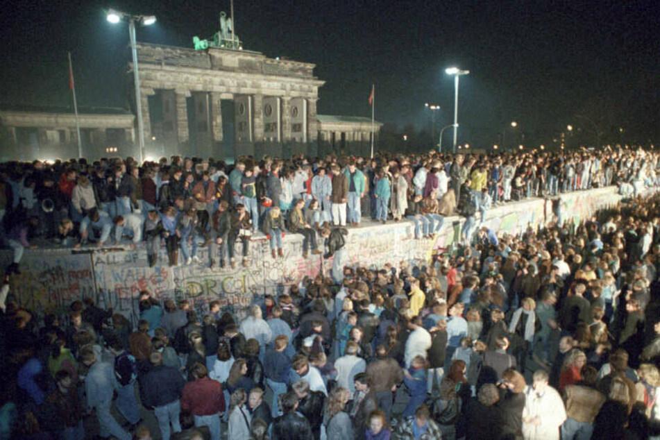 Menschen auf der Berliner Mauer vor dem Brandenburger Tor in der Nacht vom 9. auf den 10.11.1989.