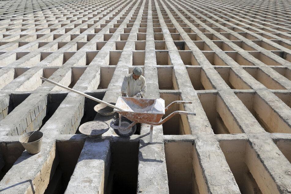 Ein Friedhofsarbeiter bereitet neue Gräber auf dem Friedhof Behesht-e-Zahra am Rande der iranischen Hauptstadt Teheran vor.