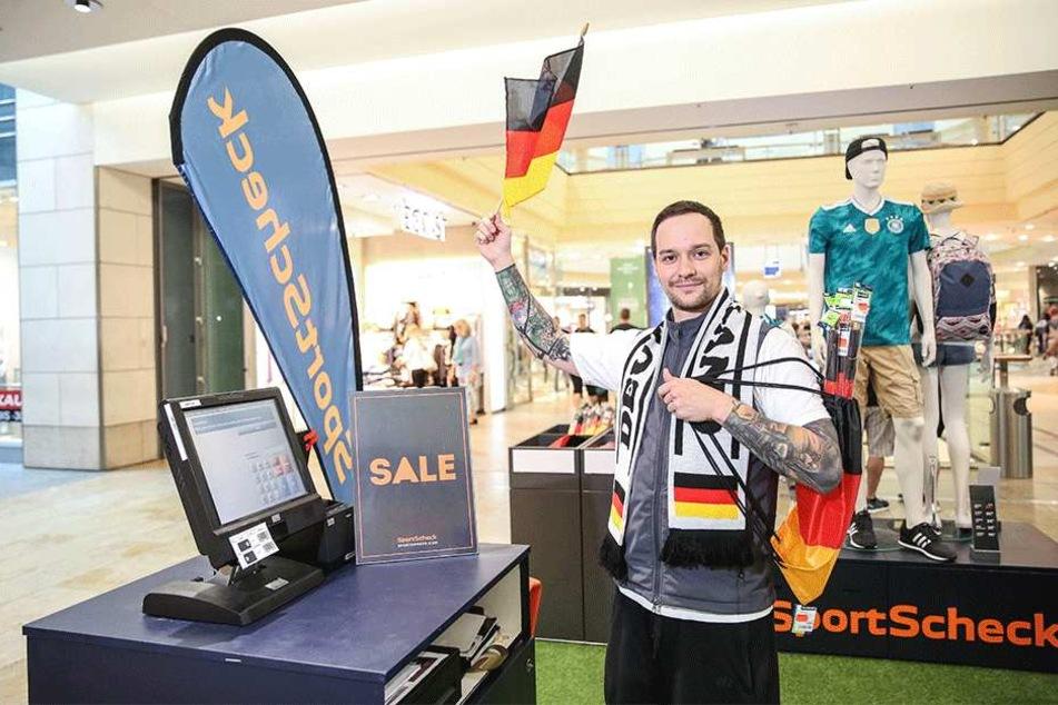 Sportscheck-Verkäufer Alex Böhm (29) hält die deutsche Fahne hoch. Das Geschäft in der Altmarkt-Galerie setzt bei Wimpeln, Beuteln, Schals und Co. auf Rabatte.